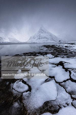 Mist on the snowy peak of Volanstinden, Fredvang, Lofoten Islands, Norway