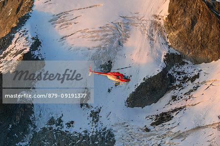 Helicopter in flight on glacier of Monte Disgrazia, Valmalenco, Val Masino, Valtellina, Lombardy, province of Sondrio, Italy