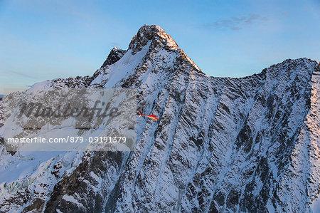 Helicopter in flight on the north face of Monte Disgrazia, Valmalenco, Val Masino, Valtellina, Lombardy, province of Sondrio, Italy