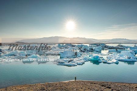 Person admiring icebergs at glacier lagoon of Jokulsarlon. Eastern Iceland, Iceland