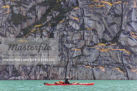 Man kayaking near cliff, Narsaq, Vestgronland, Greenland