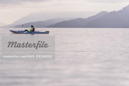 Man kayaking in lake, Johnstone Strait, Telegraph Cove, Canada