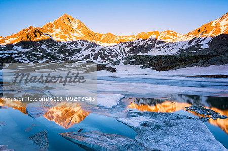 Tre Signori peak reflected in an alpine lake at thaw, Gavia Pass, Val Camonica, Stelvio National Park, Brescia Province, Lombardy, Italy, Europe