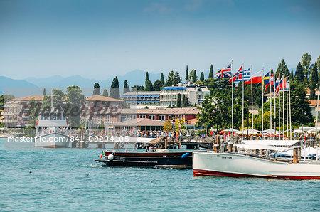 Busy marina and ferry terminal at Sirmione, Lake Garda, Lombardy, Italian Lakes, Italy, Europe
