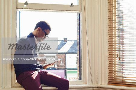 Young man reading on windowsill