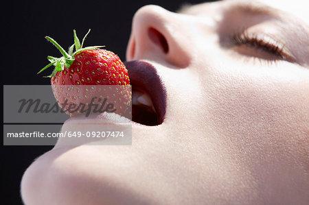 Studio head shot of young woman balancing a strawberry on lips