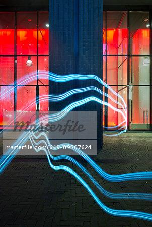 Illuminated wavy lines moving around architectural pillar