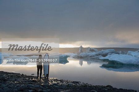 Woman with surfboard, Jokulsarlon Glacier Lagoon, Skaftafell National Park, Iceland
