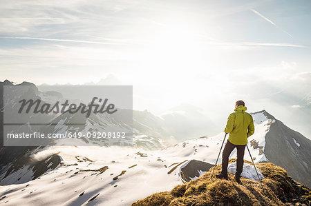 Young male mountain trekker looking from ridge in Bavarian Alps, Oberstdorf, Bavaria, Germany