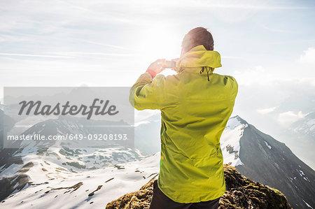 Young male mountain trekker photographing Bavarian Alps, Oberstdorf, Bavaria, Germany