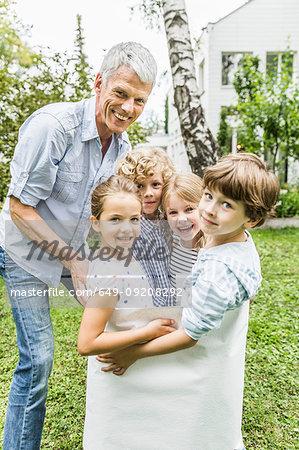 Portrait of grandfather and grandchildren in a garden sack