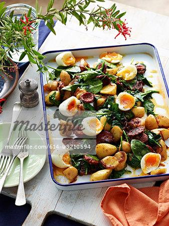 Table with tray of roast potato, chorizo and green salad