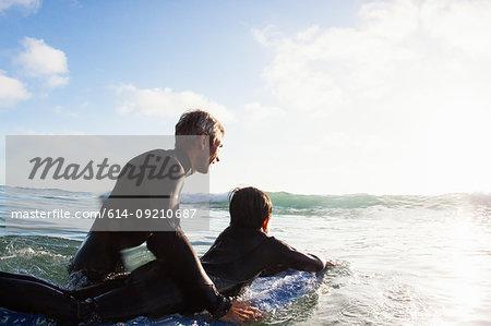 Father and son at sea with surfboard, Encinitas, California, USA