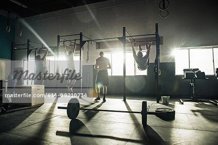 Three men training on exercise bar in gymnasium