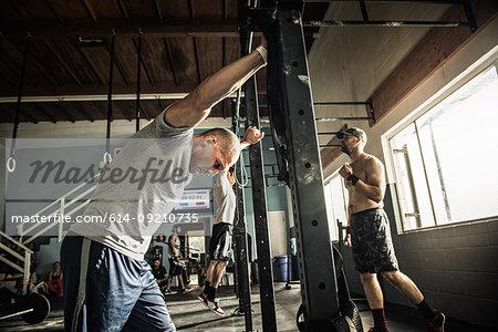 Men training on exercise bar in gymnasium