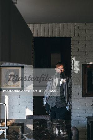 Man leaning against doorway of kitchen