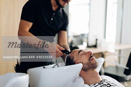 Male hairstylist washing male customer's hair in hair salon