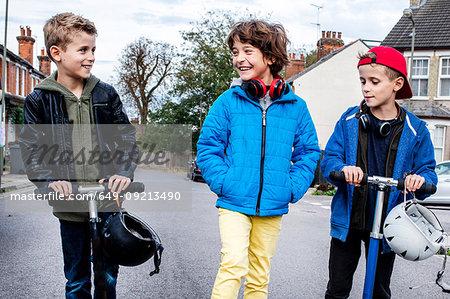 Boys riding push scooter on street