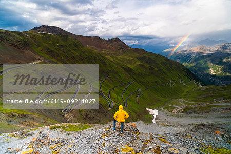 Man on rocks admires the rainbow on the winding road, Stelvio Pass, South Tyrol side, Valtellina, Lombardy, Italy, Europe