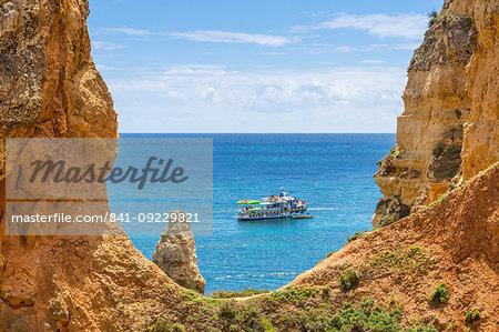 Excursion boat passing the rocky coastline near Lagos, Algarve, Portugal, Europe