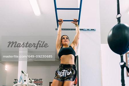 Woman swinging along monkey bars gym