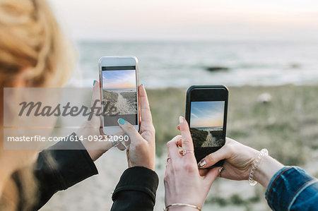 Two young women photographing beach on smartphones, over shoulder view, Menemsha, Martha's Vineyard, Massachusetts, USA