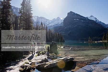 Women hiking along tranquil, idyllic mountain lake