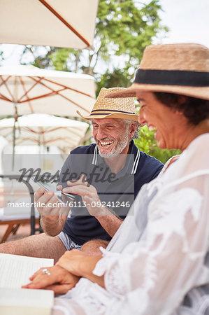 Happy mature couple using smart phone at resort poolside