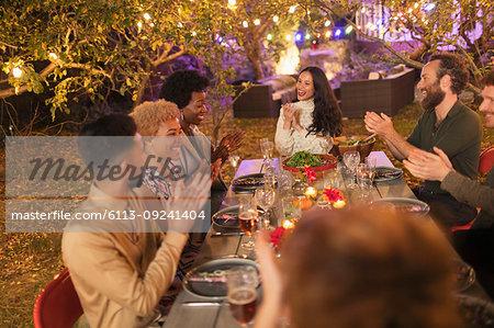 Friends clapping, enjoying dinner garden party