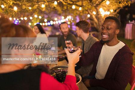 Happy friends toasting wine glasses, enjoying dinner garden party