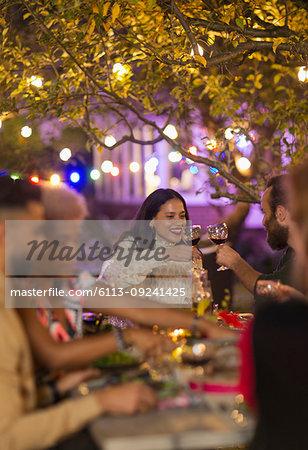 Friends toasting wine glasses, enjoying dinner garden party