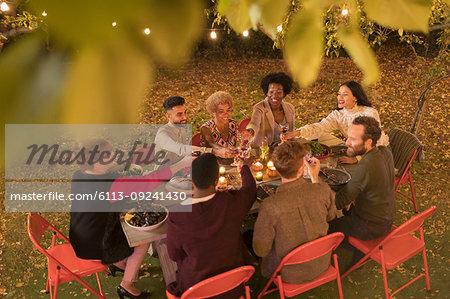 Friends toasting wine, enjoying dinner garden party