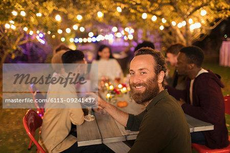 Portrait confident man drinking wine, enjoying dinner garden party