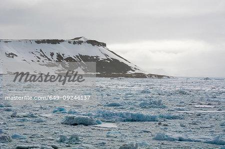 Frozen landscape and distant snow capped mountain, Wahlenberg Fjord, Nordaustlandet, Svalbard, Norway