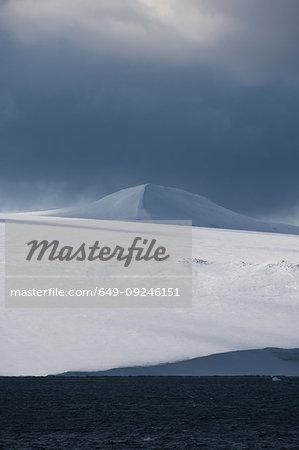 Snow covered coastal landscape with storm clouds, Hinlopen Strait, between Nordaustlandet and Spitsbergen, Svalbard, Norway