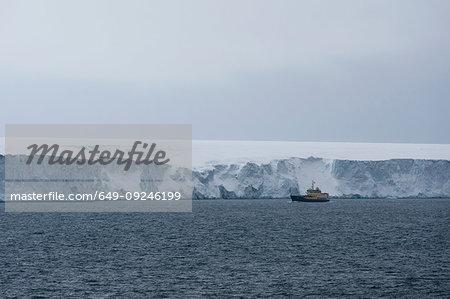 Ship passing ice cliffs of  polar ice cap, Austfonna Nordaustlandet, Svalbard, Norway
