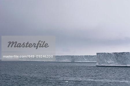 Overcast clouds over arctic ocean and ice cliffs of  polar ice cap, Austfonna Nordaustlandet, Svalbard, Norway