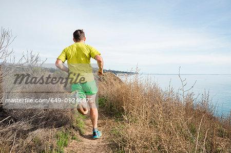 Runner jogging on cliff top, Santa Barbara, California, USA