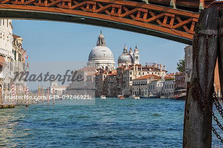 Accademia footbridge over Grand Canal with water taxis, Renaissance architectural style residential palace buildings, Santa Maria della Salute basilica, Dorsoduro, Venice, Veneto, Italy