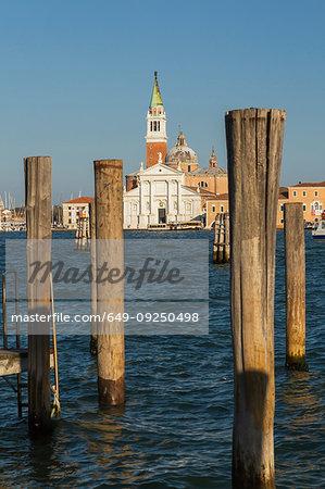 Wooden mooring posts, canal lane markers, Benedictine Church, Campanile bell tower, San Giorgio Maggiore Island, San Marco district, Venice, Veneto, Italy