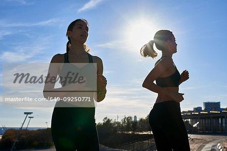 Friends jogging in sports stadium