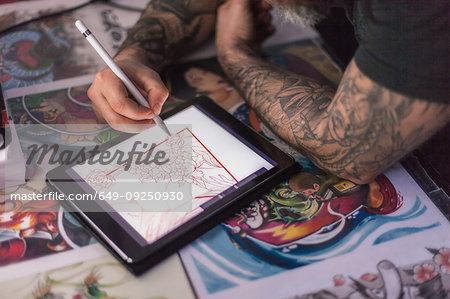 Tattooist sketching tattoo design on digital tablet