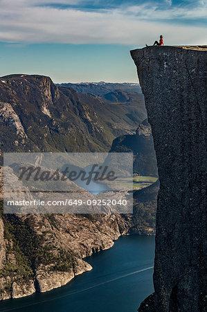Hiker enjoying view on cliff top, Preikestolen (Pulpit Rock), Lysefjord, Norway, Stavanger
