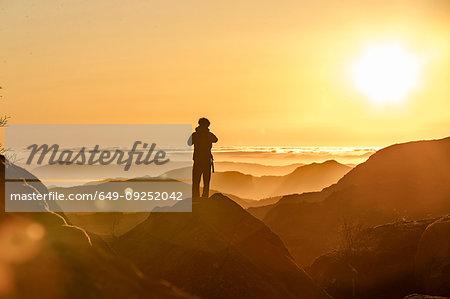 Hiker enjoying view on hilltop at sunset, Preikestolen (Pulpit Rock), Lysefjord, Norway, Stavanger