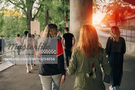 Rear view of protestors walking on street in city
