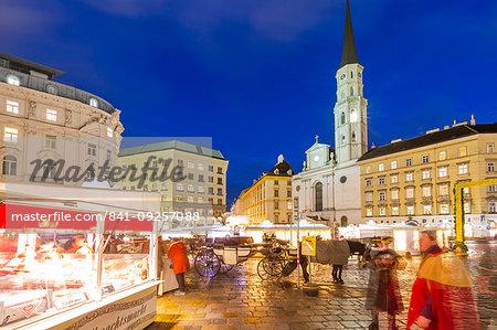 View of Christmas Markets stalls and St. Michael Catholic Church in Michaelerplatz at dusk, Vienna, Austria, Europe