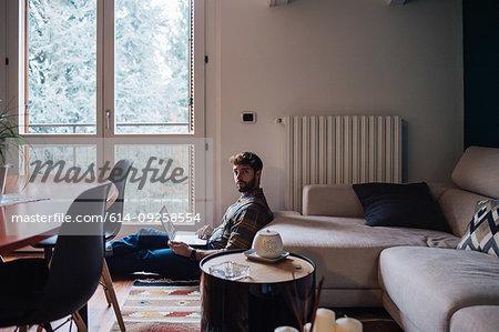 Mid adult man sitting on living room floor using laptop, portrait