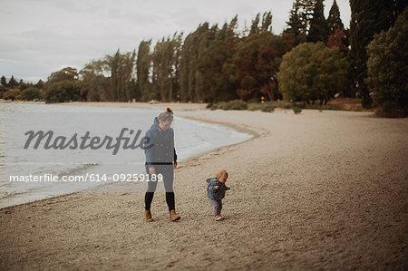 Mother and baby walking on beach, Wanaka, Taranaki, New Zealand