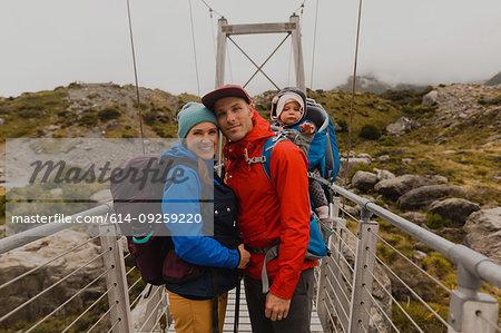 Hiker couple with baby on suspension bridge, Wanaka, Taranaki, New Zealand