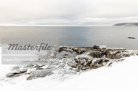Snow on rocks by lake